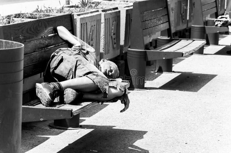 Slechte dakloze mens of vluchtelingsslaap op de houten bank op de stedelijke straat in de stad, sociaal documentair concept selec stock foto