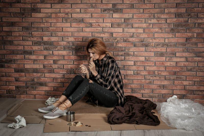 Slechte dakloze vrouw die op vloer eten royalty-vrije stock foto's