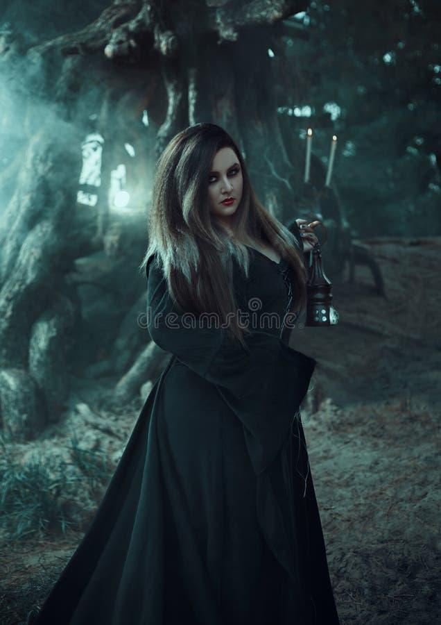 Slechte heks in een lange uitstekende kleding, die een magische lamp houden stock afbeeldingen