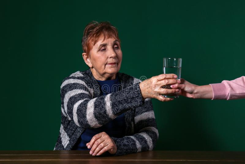 Slechte hogere vrouw die glas water nemen tegen kleurenachtergrond royalty-vrije stock foto's