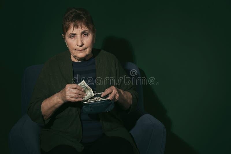 Slechte hogere vrouw met geld op kleurenachtergrond royalty-vrije stock foto's