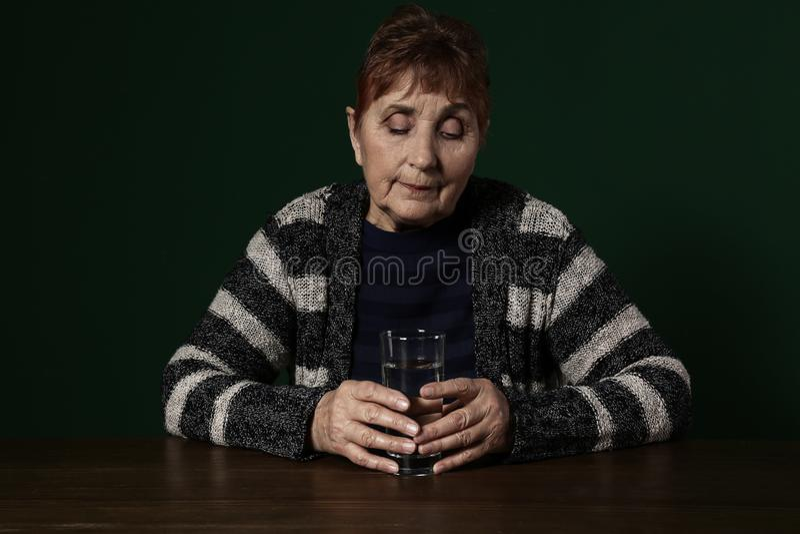 Slechte hogere vrouw met glas van waterzitting bij lijst royalty-vrije stock foto