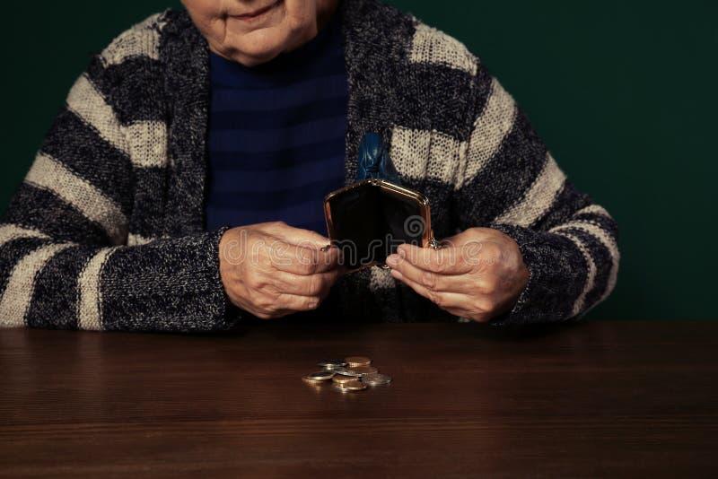 Slechte hogere vrouw met lege portefeuille en muntstukken bij lijst stock afbeeldingen