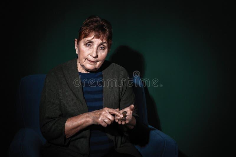 Slechte hogere vrouw met muntstukken op kleurenachtergrond stock foto's