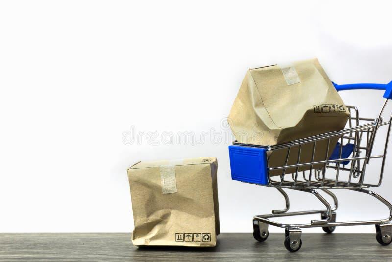Slechte leveringsconcepten Een beschadigd containervakje in klein blauw boodschappenwagentjemodel en op houten lijst met witte ac stock fotografie