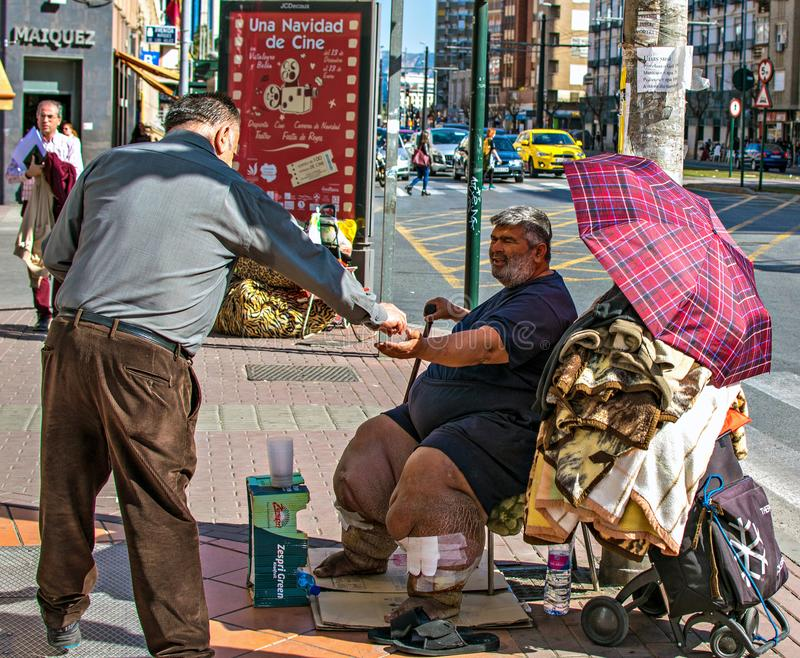 Slechte ongezonde mens die voor aalmoes in de straat van Murcia, Spanje bedelen De mens geeft geld aan armen stock afbeelding