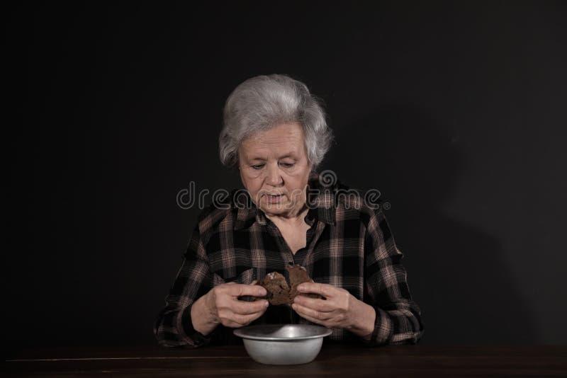 Slechte rijpe vrouw met brood en kom stock fotografie