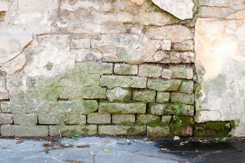 Slechte stichtingsbasis op oud huis of de de bouw gebarsten muur van de pleistervoorgevel met baksteenachtergrond royalty-vrije stock foto's