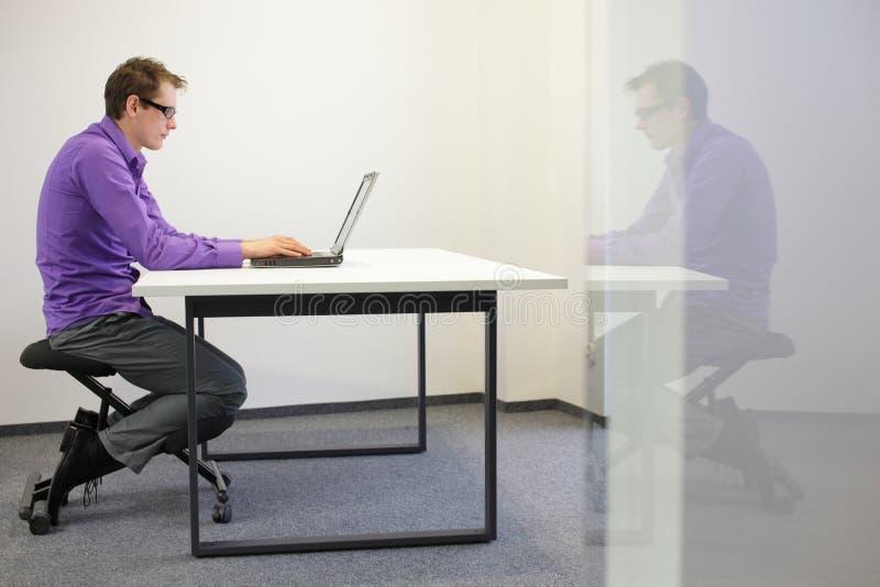 slechte zittingshouding bij werkstation. mens op het knielen stoel stock afbeelding