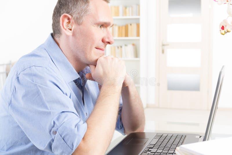 Slechthorende mens die met laptop werken royalty-vrije stock foto