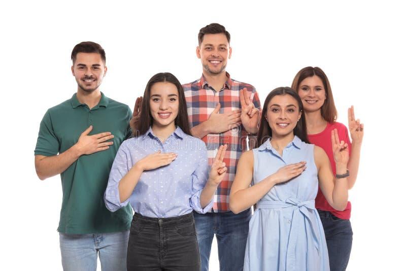 Slechthorende mensen die woordbelofte op gebarentaal tonen stock afbeelding