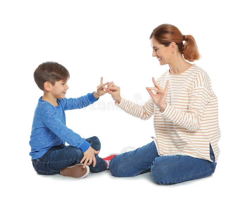 Slechthorende moeder en haar kind die met hulp van gebarentaal op wit spreken royalty-vrije stock fotografie