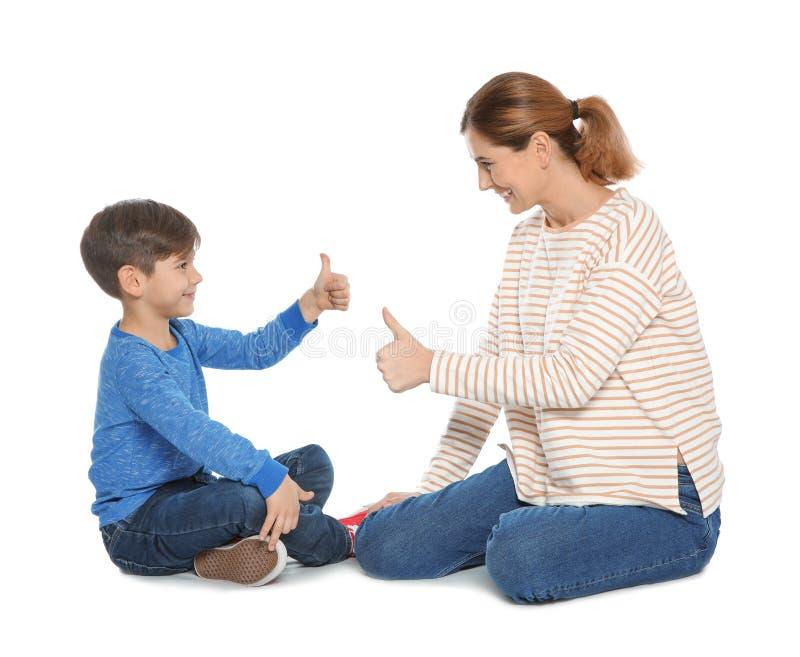 Slechthorende moeder en haar kind die met hulp van gebarentaal op wit spreken stock afbeeldingen