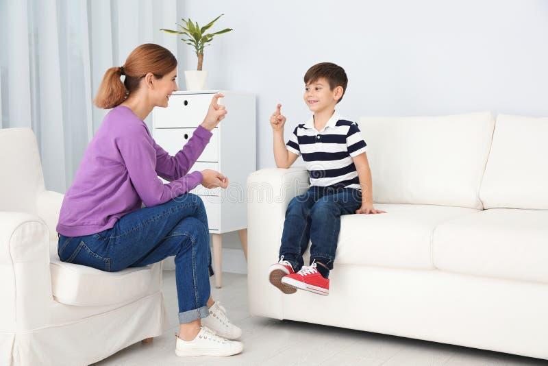 Slechthorende moeder en haar kind die met hulp van gebarentaal spreken royalty-vrije stock foto's