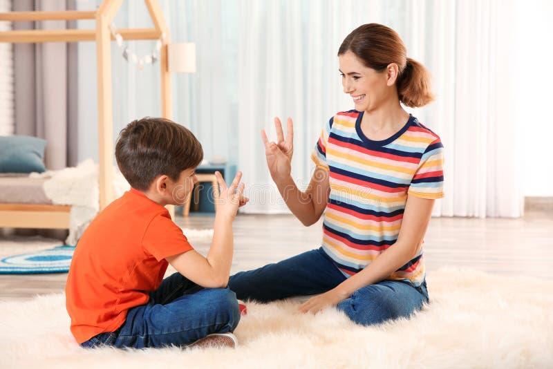 Slechthorende moeder en haar kind die met hulp van gebarentaal spreken royalty-vrije stock afbeelding