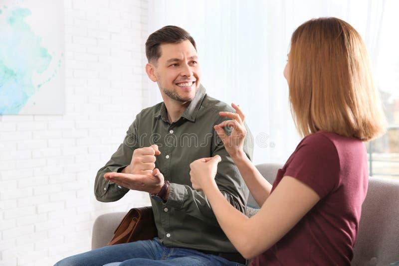 Slechthorende vrienden die gebarentaal voor mededeling over bank gebruiken royalty-vrije stock foto