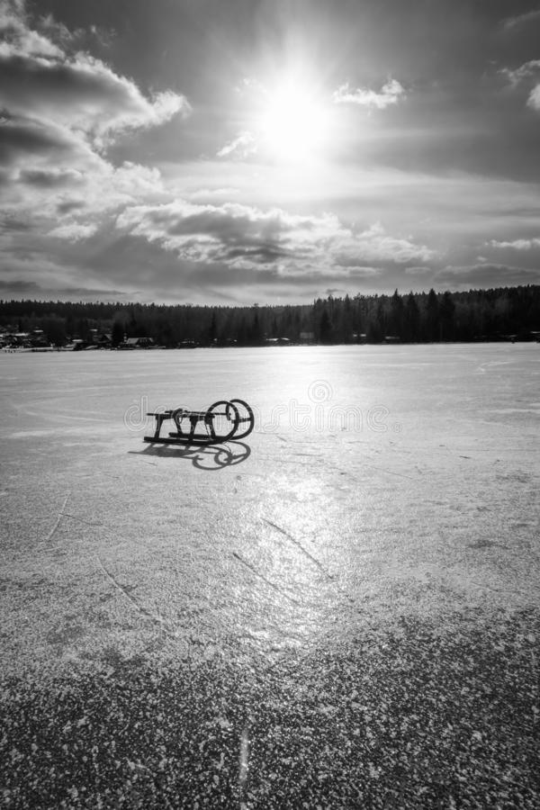 Sled on the ice. A forgotten sled on a frozen lake in the evening. The sun is shining and there are clouds in the sky on a cold day stock photo