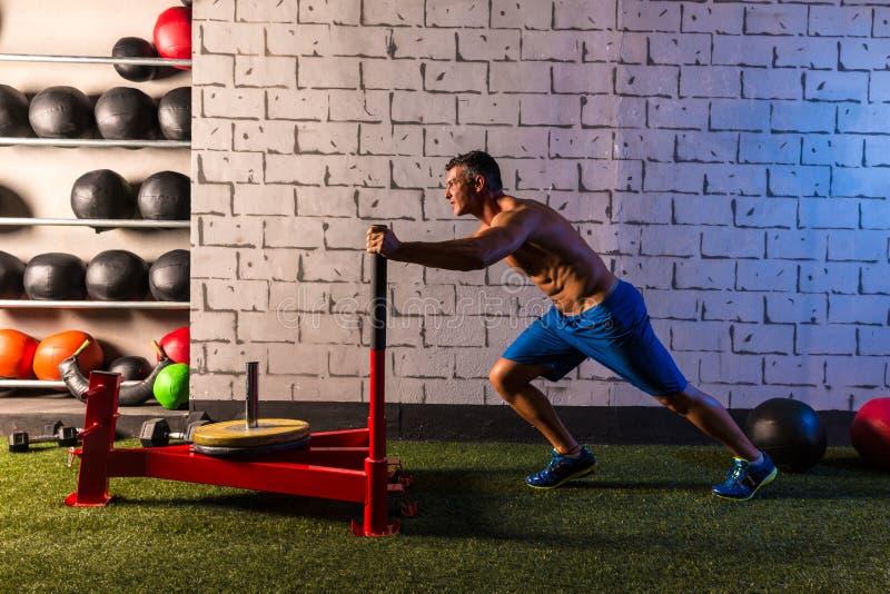Sled push man pushing weights workout. Exercise stock image