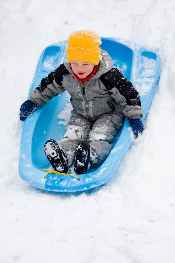 sledding下来男孩的小山 免版税库存图片