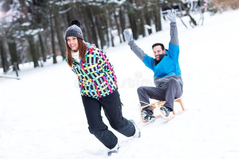 Sledding时间,夫妇享用冬时假日 库存图片