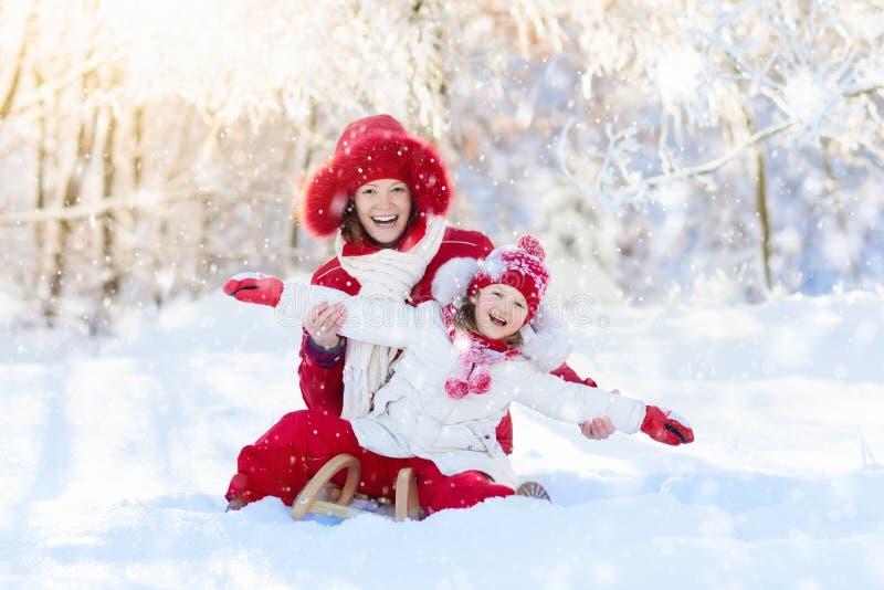 Sledding da mãe e da criança Divertimento da neve do inverno Família no trenó imagem de stock royalty free