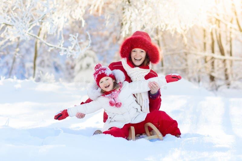 Sledding för moder och för barn Vintersnögyckel Familj på släde royaltyfri bild