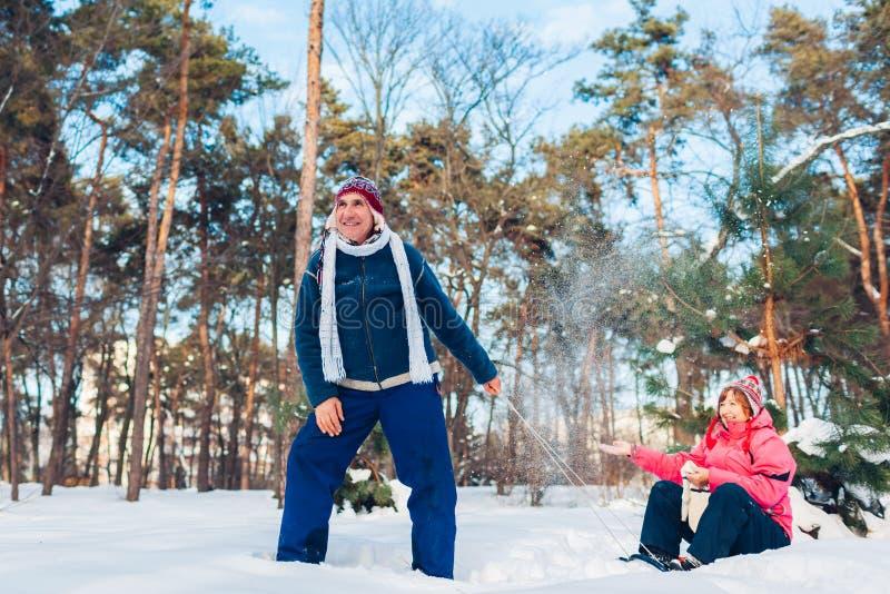 Sledding supérieur de couples Homme portant son épouse sur le traîneau Famille ayant l'amusement dans le parc d'hiver Jour du `s  photo stock
