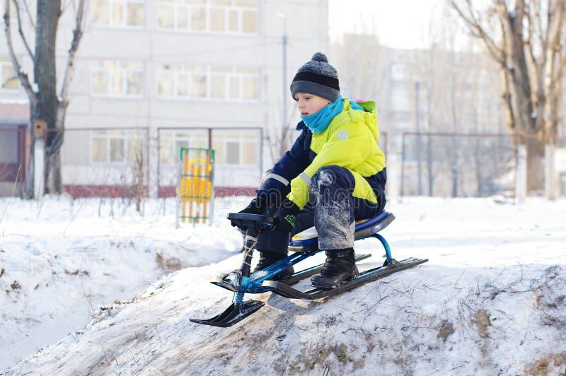 Sledding sveglio del bambino Ragazzo del bambino che guida una slitta nella neve fotografie stock libere da diritti