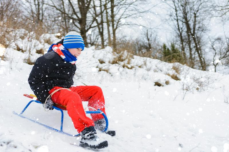 For a sledge down the boy in red pants is very happy stock photography