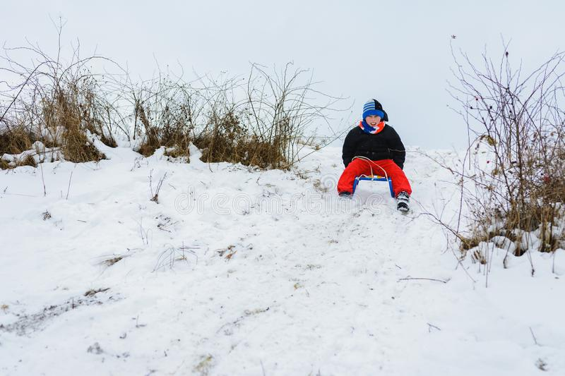 For a sledge down the boy in red pants is very happy stock photo