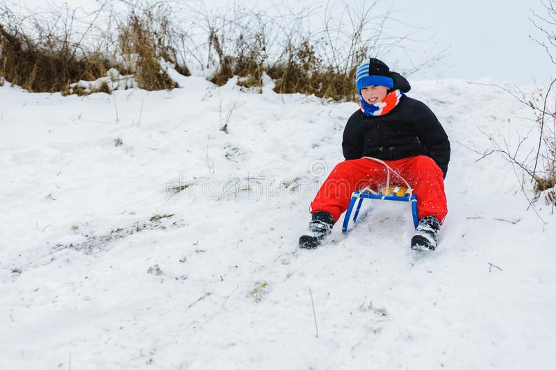 For a sledge down the boy in red pants is very happy stock image