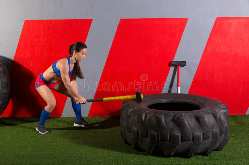 Sledgehammer Tire Hits woman workout at gym stock image