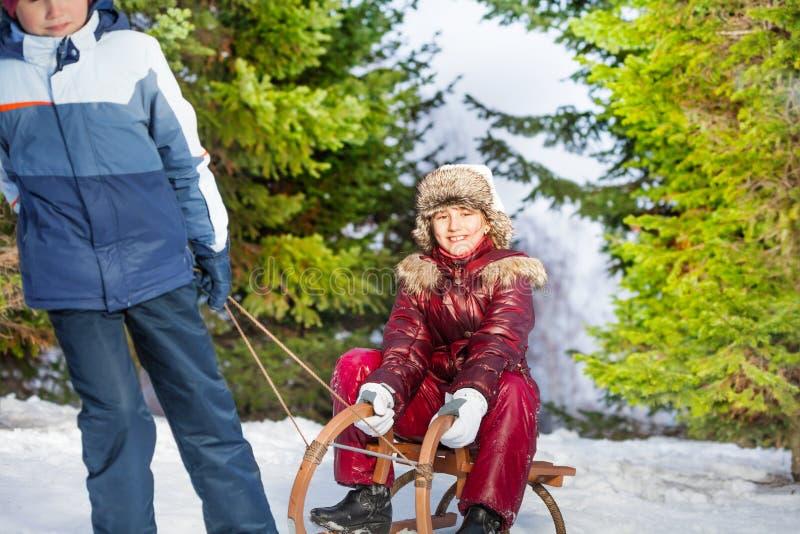 Sledging Mädchen des Jungen im Winterwald stockfoto