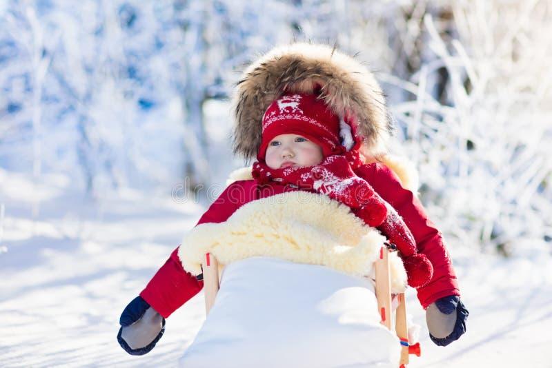 Slee en sneeuwpret voor jonge geitjes Baby het sledding in de winterpark stock fotografie