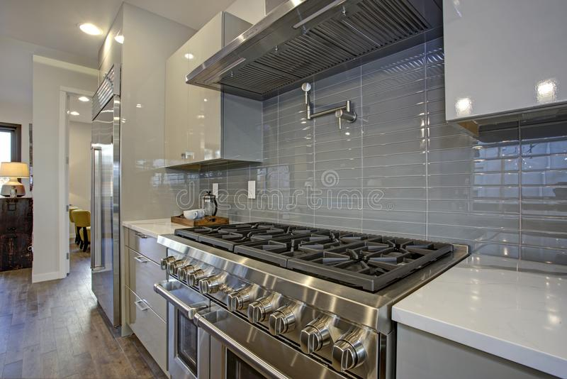 Sleek modern kitchen design with a glossy gray backsplash. Sleek modern kitchen design with a glossy gray backsplash, 8 burner range top and stainless steel stock photos