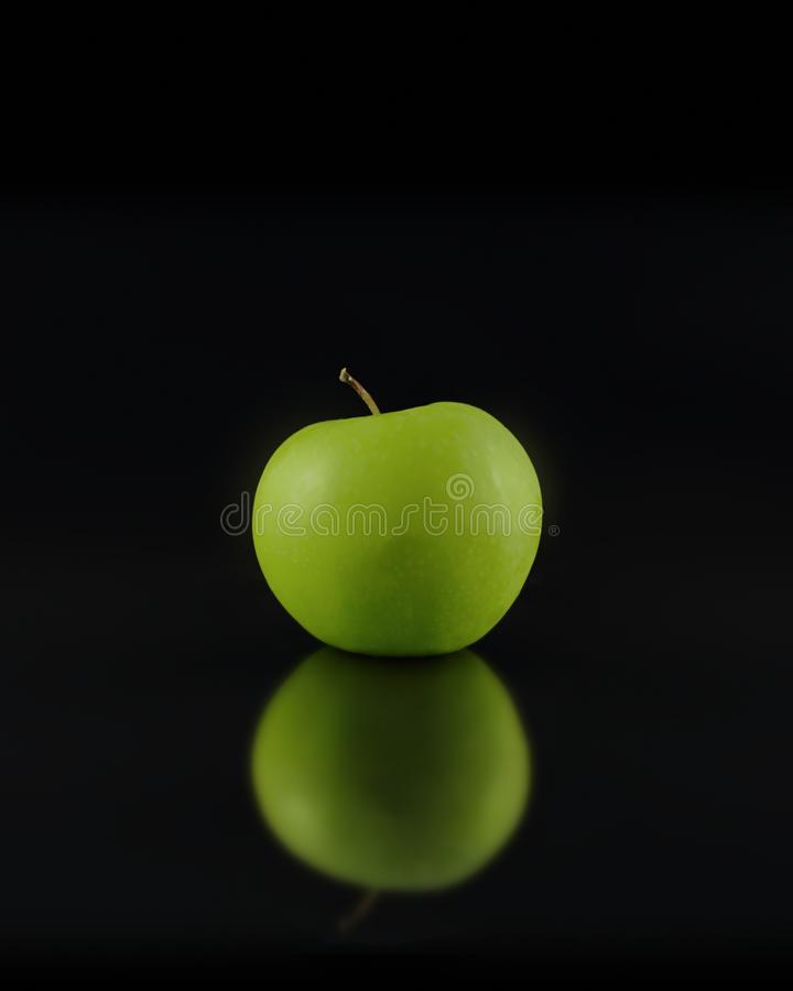 Artistic green Granny Smith apple close-up with reflection on black background. Sleek and stylish photograph featuring a close-up of a single green Granny Smith stock photo