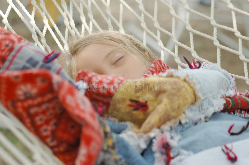 Sleep. Girl sleeps on a hammock at a camp site wrapped in a blanket stock photography