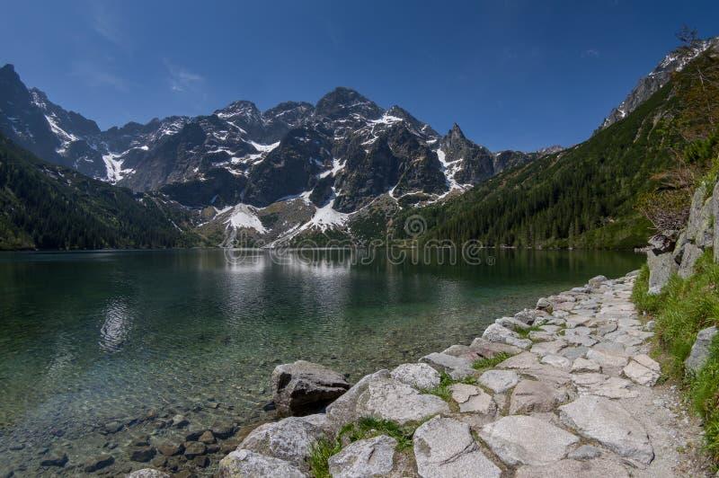 Sleep bij het bergmeer met rotsachtige die toppen in water worden weerspiegeld royalty-vrije stock foto