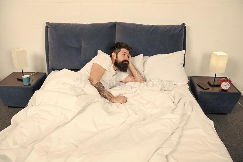 Sleep disorders concept. Man bearded hipster having problems with sleep. Guy lying in bed try to relax and fall asleep. Relaxation techniques. Violations of royalty free stock photography