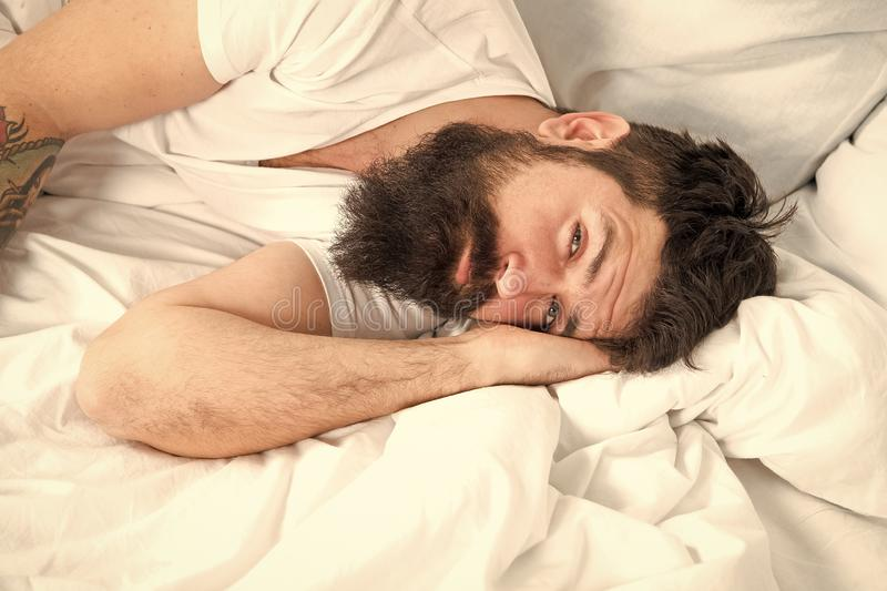 Sleep disorders concept. What a long night. Man bearded hipster having problem with sleep. Guy lying in bed try to relax. And fall asleep. Relaxation techniques stock images