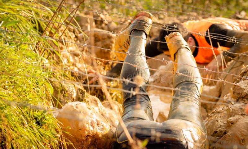 Sleep lopende atleet die een vuile vulklei kruisen onder een prikkeldraad in een modderraceauto stock afbeelding