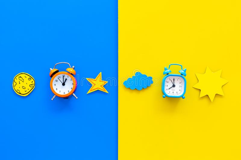 Sleep time, clock on the bed and time to awake concept. Alarm clock near sun, moon, stars cutout on blue and yellow. Background top view stock image