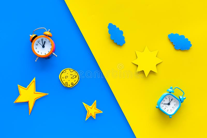 Sleep time, clock on the bed and time to awake concept. Alarm clock near sun, moon, stars cutout on blue and yellow. Background top view stock images