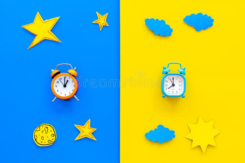 Sleep time, clock on the bed and time to awake concept. Alarm clock near sun, moon, stars cutout on blue and yellow. Background top view stock photos
