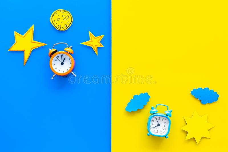Sleep time, clock on the bed and time to awake concept. Alarm clock near sun, moon, stars cutout on blue and yellow. Background top view royalty free stock photo