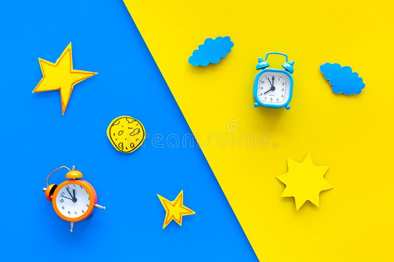 Sleep time, clock on the bed and time to awake concept. Alarm clock near sun, moon, stars cutout on blue and yellow. Background top view royalty free stock image