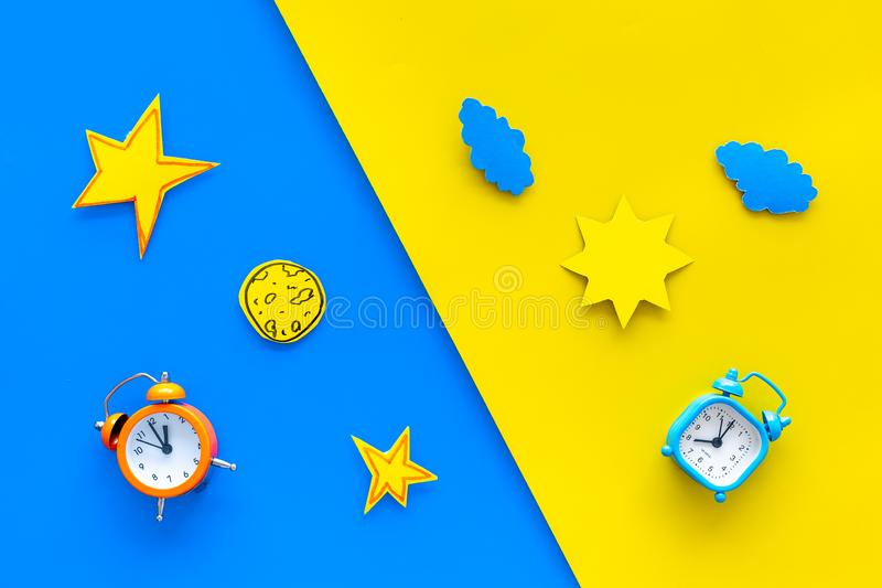 Sleep time, clock on the bed and time to awake concept. Alarm clock near sun, moon, stars cutout on blue and yellow. Background top view royalty free stock photos