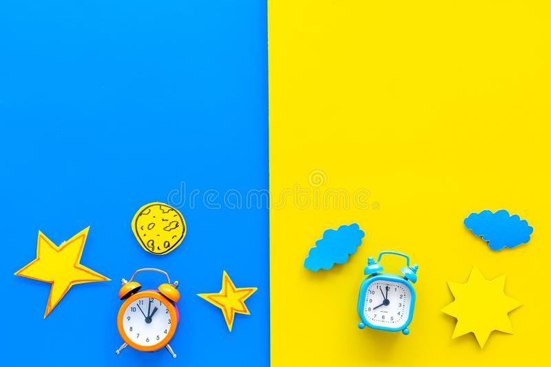 Sleep time, clock on the bed and time to awake concept. Alarm clock near sun, moon, stars cutout on blue and yellow. Background top view stock photo