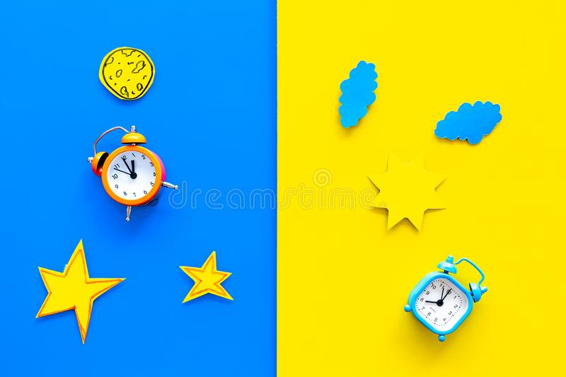 Sleep time, clock on the bed and time to awake concept. Alarm clock near sun, moon, stars cutout on blue and yellow. Background top view royalty free stock photography