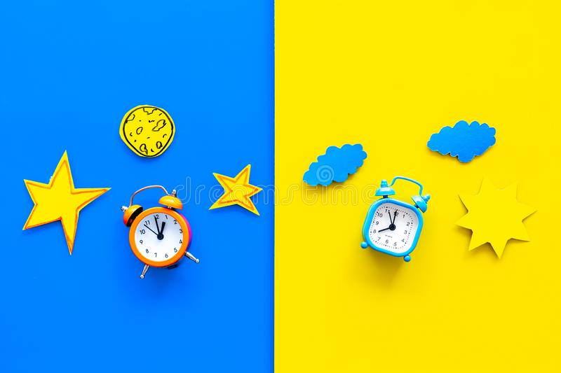 Sleep time, clock on the bed and time to awake concept. Alarm clock near sun, moon, stars cutout on blue and yellow. Background top view royalty free stock images